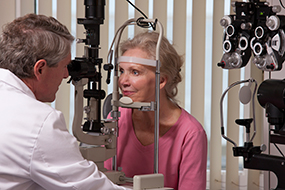 Ophthalmologist examining a womans eyes with a slit lamp.
