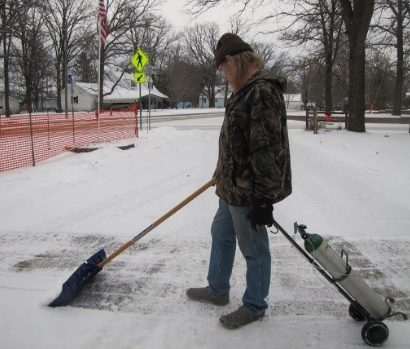 Ken shoveling snow in his yard while holding his oxygen tank.