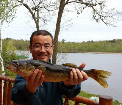 Smiling man holding a fish with both hands next to a lake.