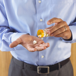 Man pouring pills in his hand