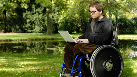 a person working on his laptop sittting in a wheelchair in a park