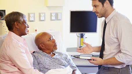 an elderly couple getting advice from a doctor in a hospital