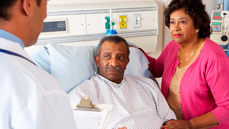 a husband laying in a hospital bed and listening with his wife to the doctor
