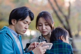 Man and woman look at smart phone screen while the woman holds a small child.