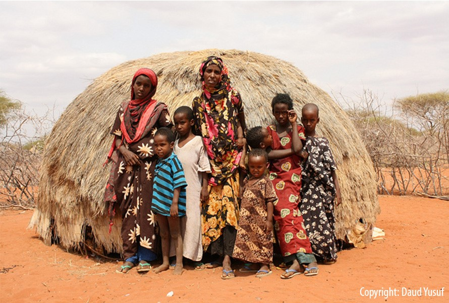 Kenyan children standing in front of a hut.