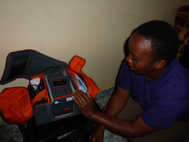 A lab technician performs quality control measures on the PIMA CD4 Analyser before going out for data and specimen collection.