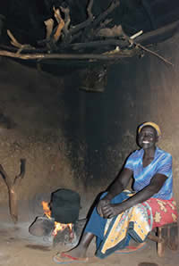 Women traditionally use a 3-stone stove indoors for cooking in Kenya