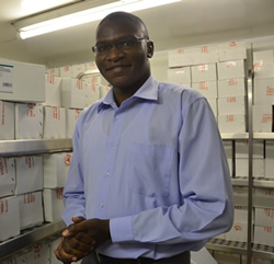 Kenyan medical epidemiologist Tamu Collins standing in a storage room filled with tetanus vaccine