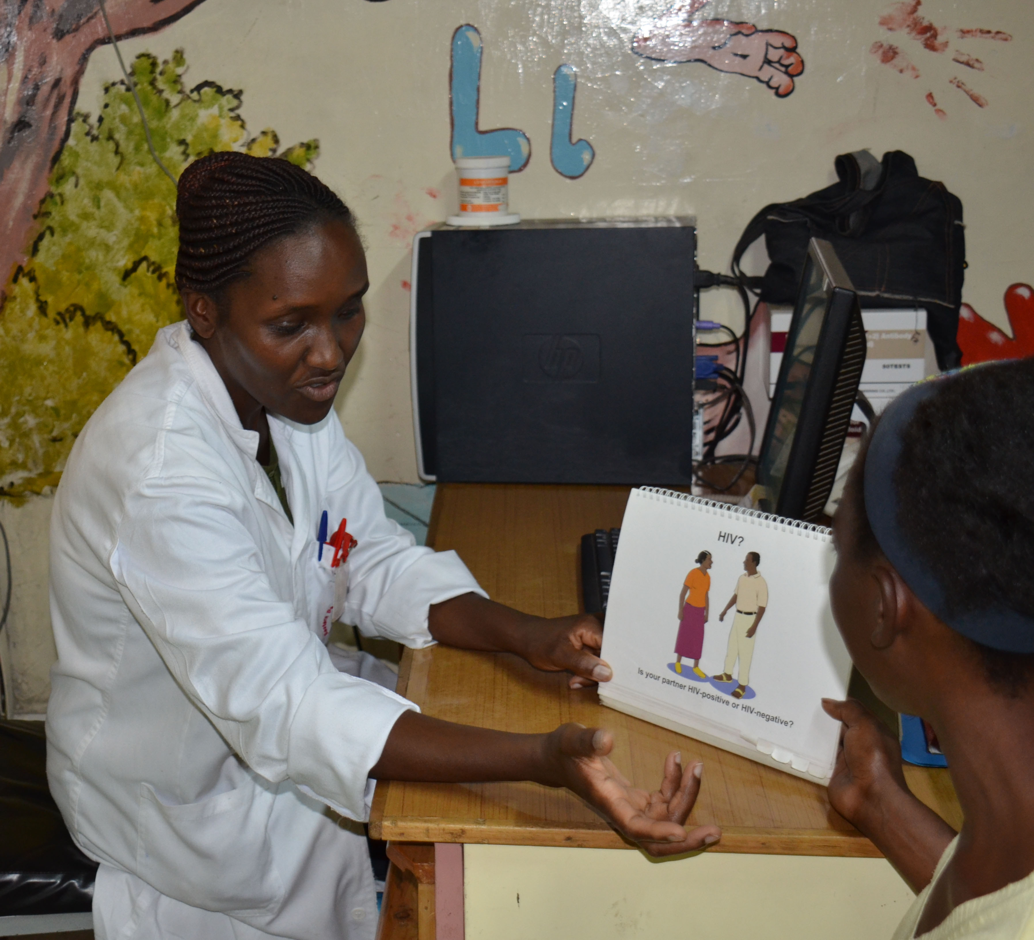 Jelius Muraguri, PMTCT nurse at EDARP, discusses HIV prevention and care with one of the mothers attending CDC- supported Komarock Clinic