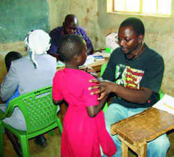 CDC staff David Ousu (clinician) and Dr. Joash Gombe (pediatrician) assisting with a free medical camp held in Uluthe, Ugunja District in November 2009
