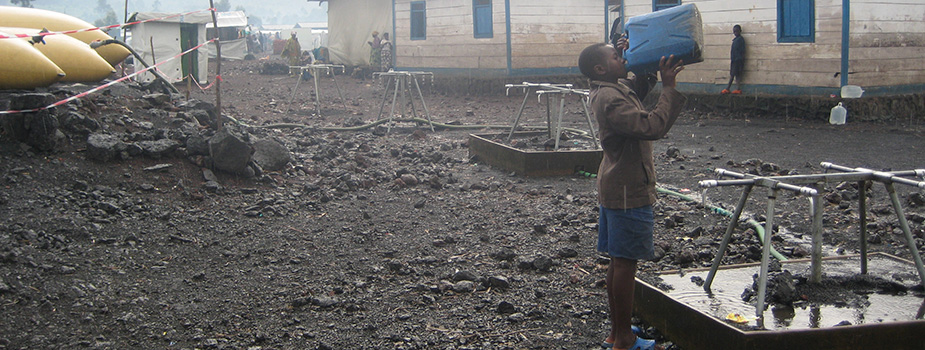 A young boy drinks water at a water collection point in an internally displaced persons camp in Goma, Democratic Republic of Congo during a cholera outbreak. Photo by Tom Handzel (2008).