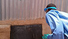 NRC team member opens the closed vault (stored fecal waste) of a UDDT for sampling