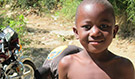 A boy by a road in Haiti, where geographic information systems save lives and money for healthcare facilities (Source: CDC)