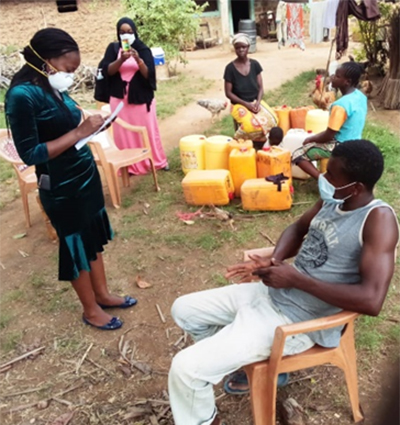 FELTP resident interviewing a close contact of a confirmed COVID-19 case outdoors in Rabai subcounty, Kenya.