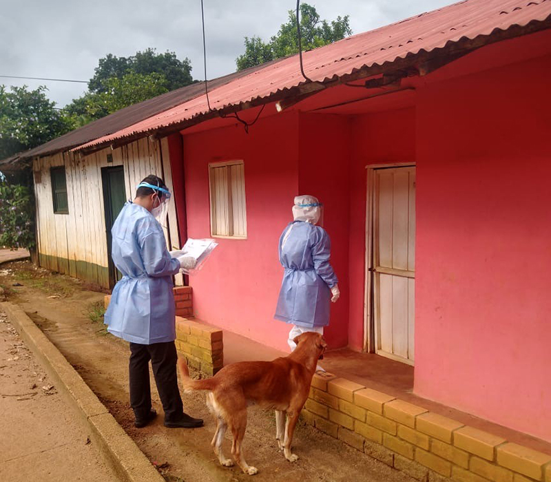 Two FETP residents conducting contact tracing in Mitu village, Vaupes, Colombia (border with Brazil) the first eleven COVID-19 cases were detected. A brown dog is near one of the residents.