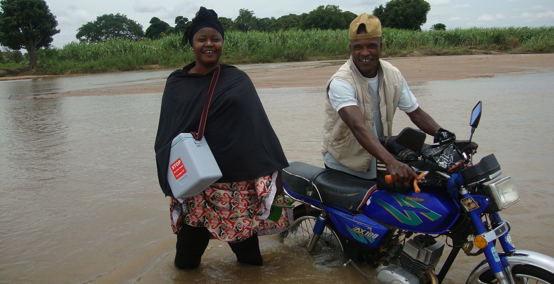 Dr. Endie Waziri crossing a river in Nigeria to vaccinate children against polio. Photo: NSTOP Team
