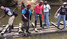 Liberian disease detective trainees carefully cross a river on a long raft to reach remote settlements