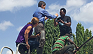 CDC Director Dr. Tom Frieden on top of a water tank in Tanzania with public health colleagues