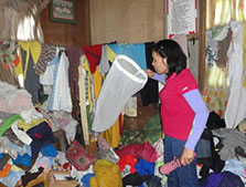 An entomologist examining whether an adult mosquito was caught amidst a sea of clothes. Photo taken during an entomologic survey conducted during a Chikungunya virus fever outbreak. Davao City, Philippines, October 2011.
