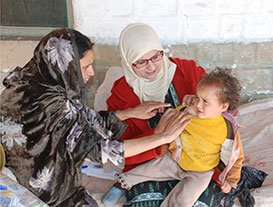 Pakistan FELTP resident Dr. Najma Javed checks for the Bacillus Calmette-Guérin (BCG) vaccine scar on the shoulder of a young child. The BCG vaccine protects children against tuberculosis.