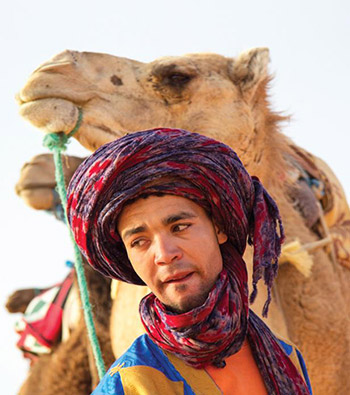 Man wearing multi-colored turban with camels. Photo: Getty
