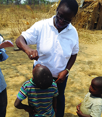 Dr. Aissata Daiha from CDC's Global Immunization Division administering the oral polio vaccine in a remote area of Lumbumbashi. Photo: Louie Rosencrans, CDC.