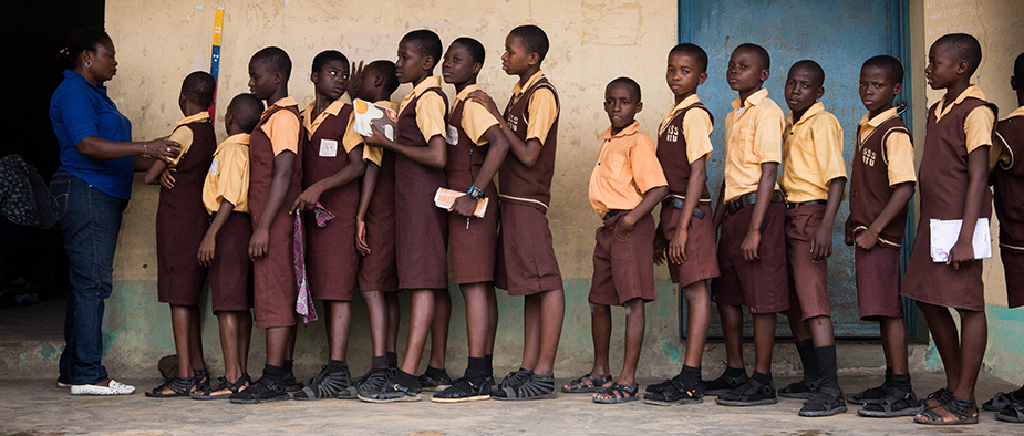 Students from Atu Government School in Calabar, Nigeria, receive medicines for NTDs during a mass drug administration. Photo: Ruth McDowall, RTI International.