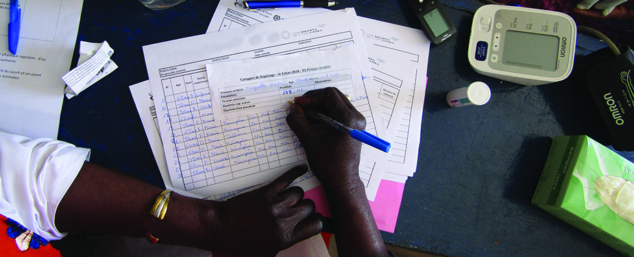 A health worker completes patient paperwork at a clinic. Photo: Cheick Niang.