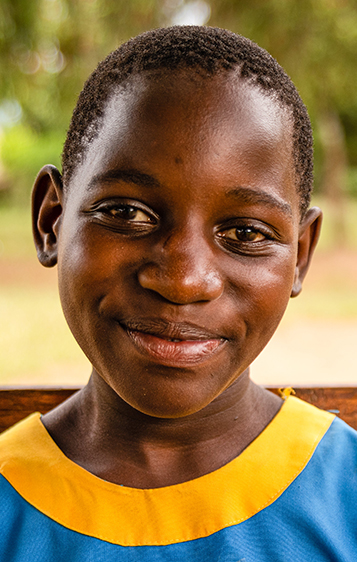 An 11-year old student from Luwero, Uganda, seated outside in front of her school.  Photo: RTI International