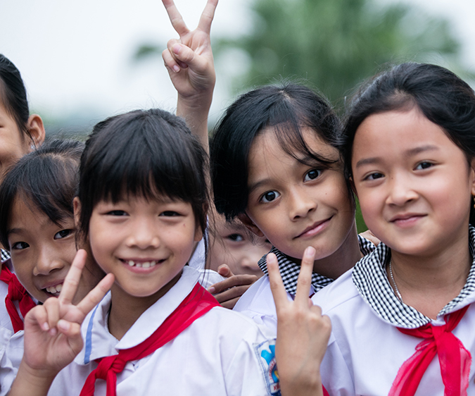 A group of school kids in Vietnam smile and pose for the camera. Photo: RTI International