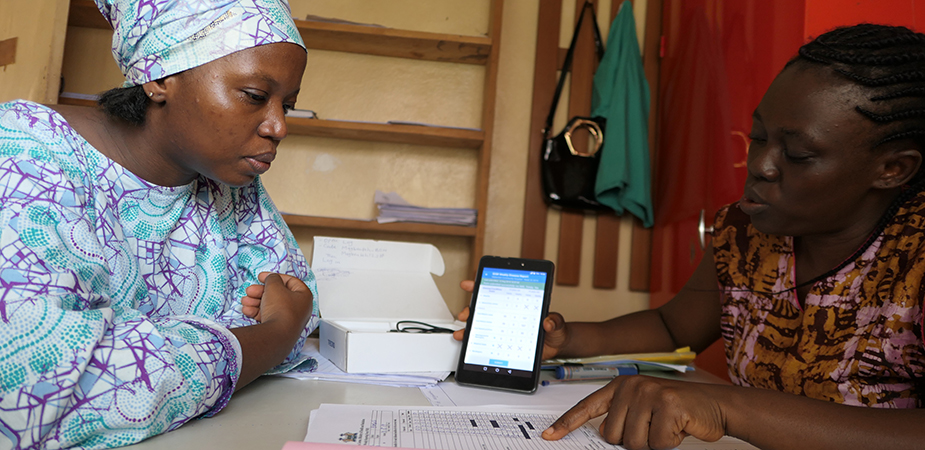 Local health worker demonstrating eIDSR to CDC's Fanny Koroma (in blue) during a field site visit. Photo: Julia Chen