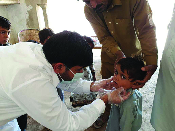 Child receiving polio examination from medical professional.