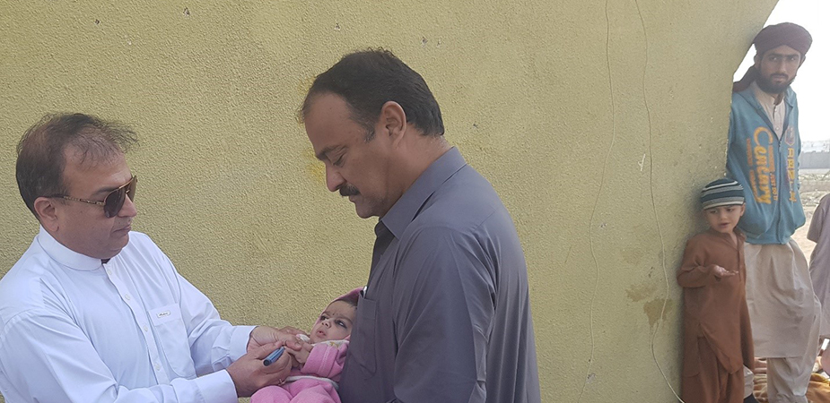 Infant receiving polio vaccine during local vaccination campaign.