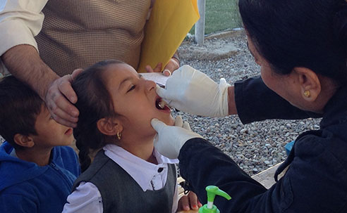 Girl receiving oral cholera vaccine in a camp for displaced Iraqis, Erbil Iraq (Source: Eugene Lam, CDC)