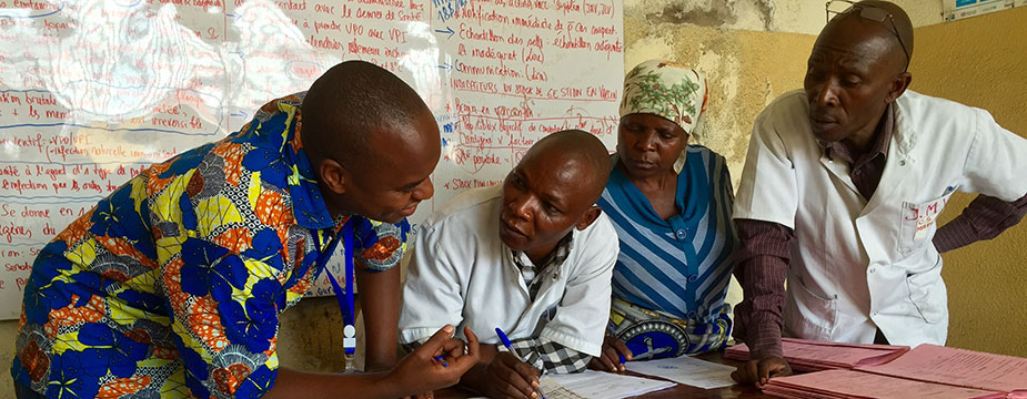 While reviewing maternal and newborn health records with a midwife (center) in Goma, DRC, she had to leave twice to deliver babies (Source: Alaine Knipes, CDC)
