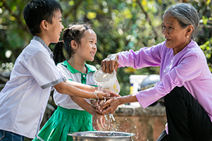 An elderly woman in Vietnam pouring water with one hand and using the other to help a boy and a girl wash their hands. Photo: Scott McPherson, RTI International
