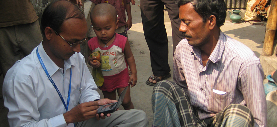 A field epidemiologist interviews a man in a Bangladeshi village. Field epidemiologists collect and analyze health data as well as assist during emergencies.