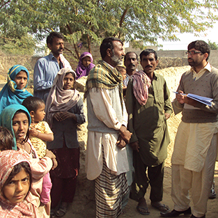 Epidemiologist and villager in discussion in Pakistan, surrounded by children and other men from village.