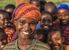 A child in a brightly colored headwrap smiles at the camera, with a group of children smiling in the background.
