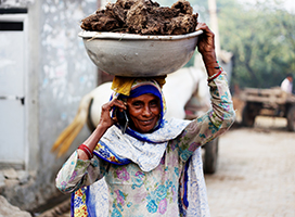 A petite woman speaks on the phone while transporting materials in a large container balanced on her head.