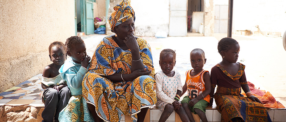 A family watches a trachoma surveillance survey at their home in the village of Merina Mboupbene, Kébémer Department, Senegal on February 22, 2017. Teams composed of Ministry of Health staff and RTI staff traveled to Kébémer to carry out a trachoma surveillance survey. The activity includes household visits to assess the eyelids of community members to check for any signs of ongoing transmission of trachoma.  Kébémer was previously considered endemic for trachoma, but a recent impact survey found that the prevalence was below 5%, meaning treatment is no longer required. This survey assesses if there is any recurrence of transmission, or if the districts is on track to eliminate the disease.