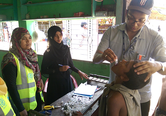 Dr. Mostafa Moin Uddin, IMPACT-Bangladesh graduate, delivering oral cholera vaccine to a Rohingya child in the Cox Bazar refugee camp helps to prevent the spread of this dangerous disease. Photo: Dr. Nurullah Awal, IMPACT-Bangladesh