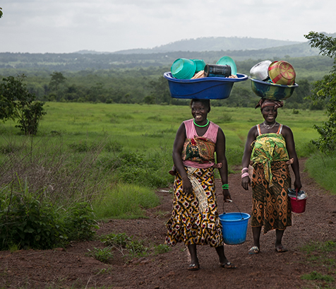 Two women from Guinea carrying children on their backs and balancing laundry dishes on their heads. Photo: Scott McPherson, RTI International