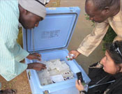 "A ""cold chain"" officer (left) in Nigeria checks to be sure polio vaccine vials are correctly packed."