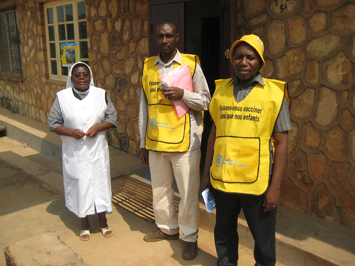 Cameroon: Members of the vaccination team (center and right) at a health center to vaccinate children. On the left is the director of the health facility.