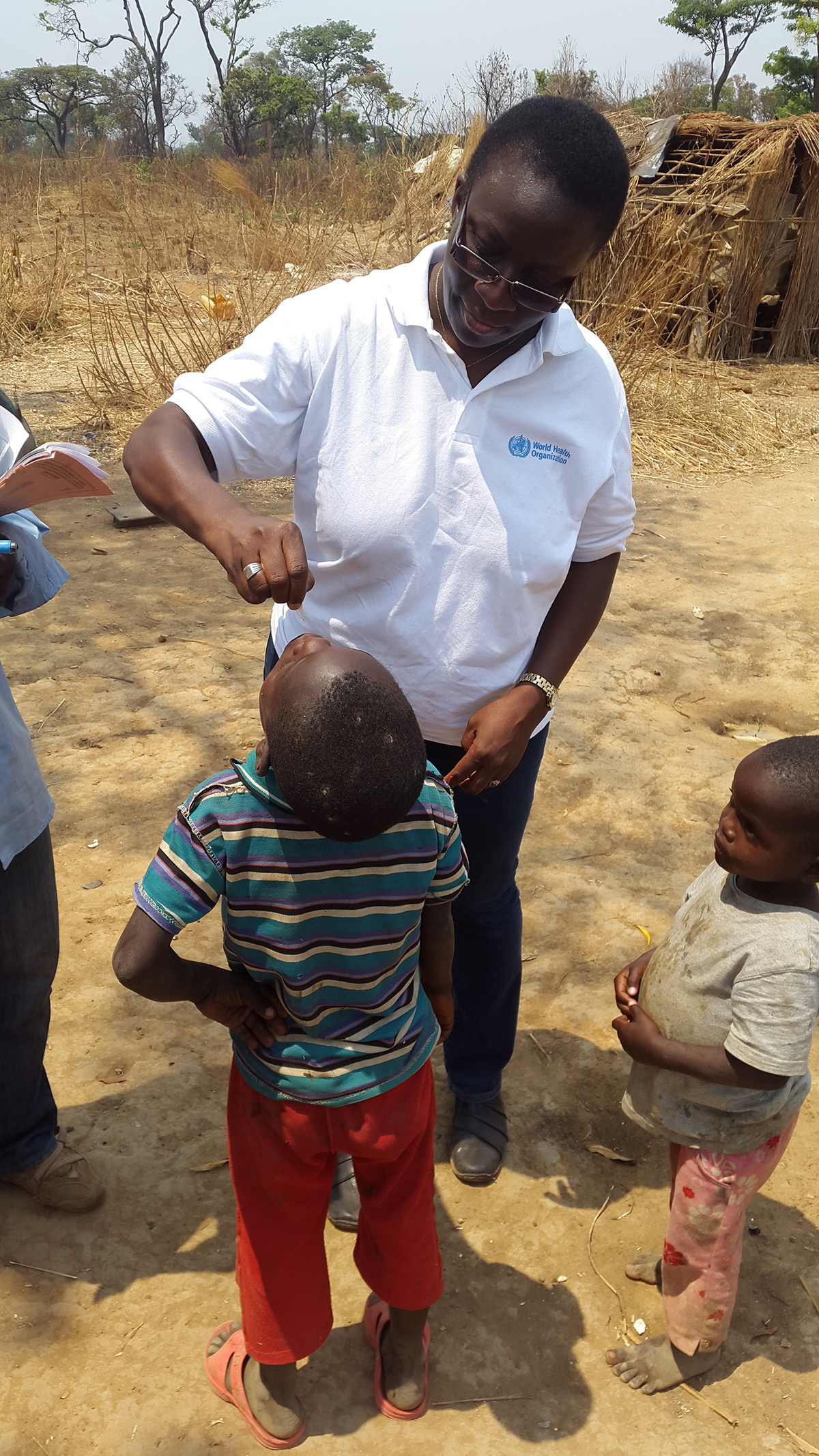 Democratic Republic of the Congo: Dr. Aissata Diaha from CDC's Global Immunization Division administering the oral polio vaccine to a child during the polio immunization campaign in a remote area of Lubumbashi.