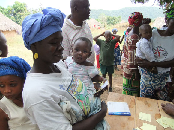A mom with her child standing in line to receive the vaccine to protect against deadly yellow fever in Sierra Leone.