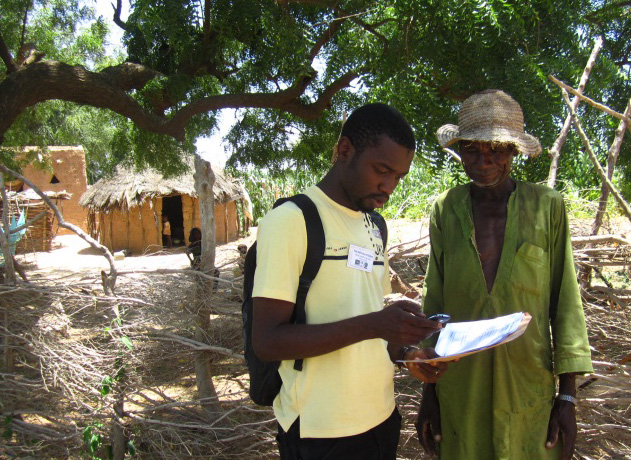 Data collector records latitude and longitude coordinates in a rural village in Sokoto State, Nigeria.