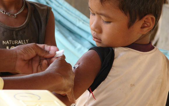 Boy in Cambodia bravely receiving his measles shot.