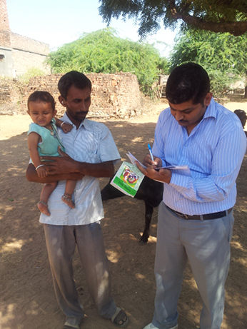 Division coordinator checking village vaccination status for feedback to auxiliary nurse-midwife. Photo courtesy of Alice Pope, CDC.